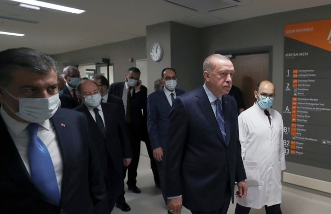 In this photo provided by the Turkish Presidency, Turkey's President Recep Tayyip Erdogan, front center, arrives to attend the inauguration ceremony for Basaksehir Pine and Sakura City Hospital, in Istanbul, Thursday, May 21, 2020.