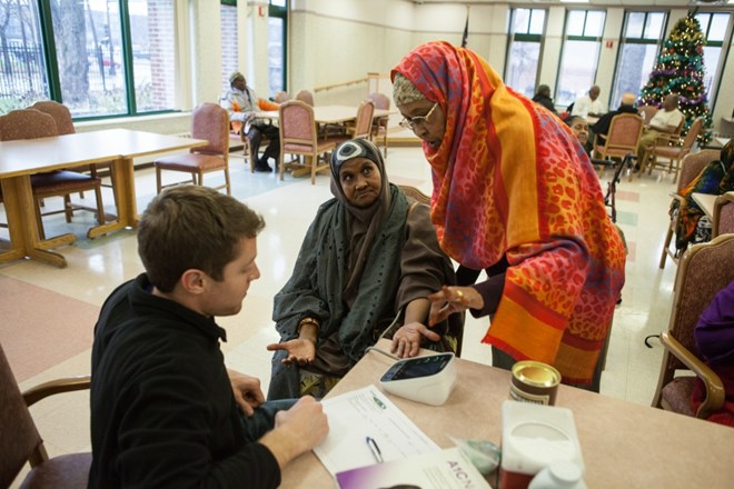 Sahra Ali, right, checks the blood pressure of an elderly Somali woman at a high-rise in South Minneapolis on December 8, 2015. It was part of a health outreach program that ended in early 2017.