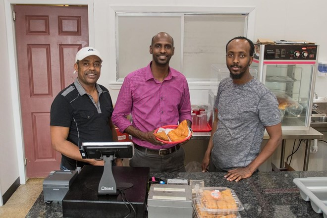 From left, Abdella Namo, Mohamed Ahmed and Ahmed Musse behind the counter at Brothers Restaurant and Grocery. Ahmed holds a basket of sambusa, an African pastry filled with ground meat or vegetables. Photo by Jackson Forderer