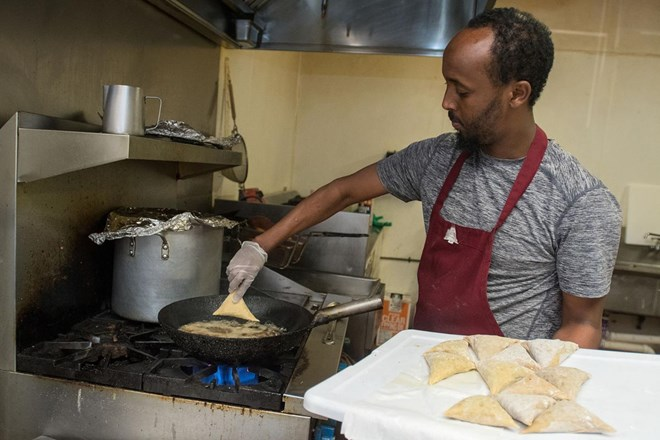 Ahmed Musse puts sambusa into a frying pan in the kitchen at Brothers Restaurant and Grocery. Sambusa is an African pastry filled with ground meat or vegetables. Photo by Jackson Forderer