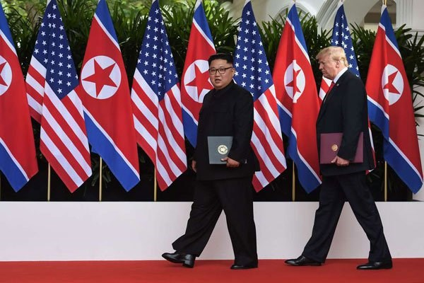 US President Donald Trump (right) walks out with North Korea's leader Kim Jong Un (L) after taking part in a signing ceremony at the end of their historic US-North Korea summit, at the Capella Hotel on Sentosa island in Singapore on June 12, 2018. PHOTO | POOL | ANTHONY WALLACE | AFP