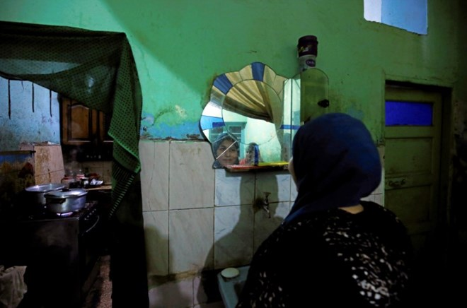 Esraa Salah, 15, looks at herself in the mirror at her home in Alwasata village of Assiut Governorate, south of Cairo, Egypt, February 8, 2018. Picture taken February 8, 2018. REUTERS/Hayam Adel