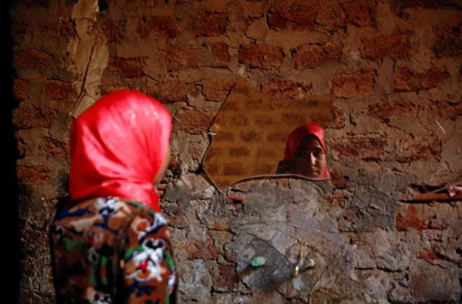 Amany Shamekh, 16, looks at herself in the mirror at her home in Awlad Serag village of Assiut Governorate, south of Cairo, Egypt, February 8, 2018. Picture taken February 8, 2018. REUTERS/Hayam Adel