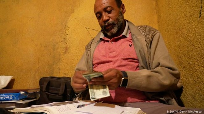 Trader Jarra Teklay Yohannes counts the day's income